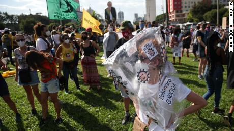 Demonstrant nosí transparent obviňující Bolsonara z genocidy.