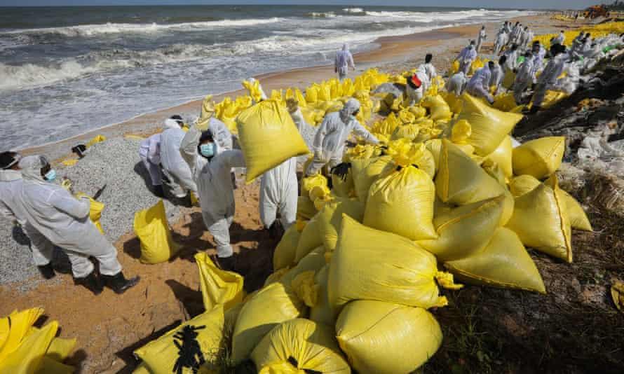Pracovníci srílanského námořnictva na sobě čisticí zařízení na pláži se žlutými taškami naplněnými troskami