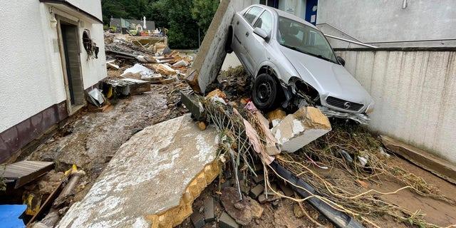 Štěrk pokryl ulici v německém městě Bad Muenstrifel, ve čtvrtek 15. července 2021, po silném dešti a povodni řeky Erft.  Lidé zemřeli a desítky jsou v Německu nezvěstné poté, co přívalové povodně proměnily potoky a ulice na zuřící přívaly, odplavily automobily a způsobily kolaps některých budov.  (B & S / dpa přes AP)