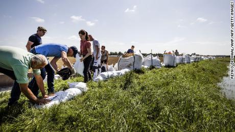 Lidé staví protipovodňové zábrany pomocí pytlů s pískem po silných deštích a povodních v nizozemském Limburgu.