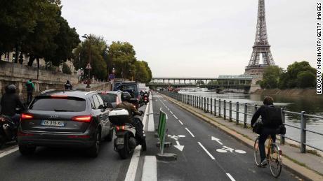 Cyklisté jezdí v rušném provozu podél řeky Seiny v Paříži.